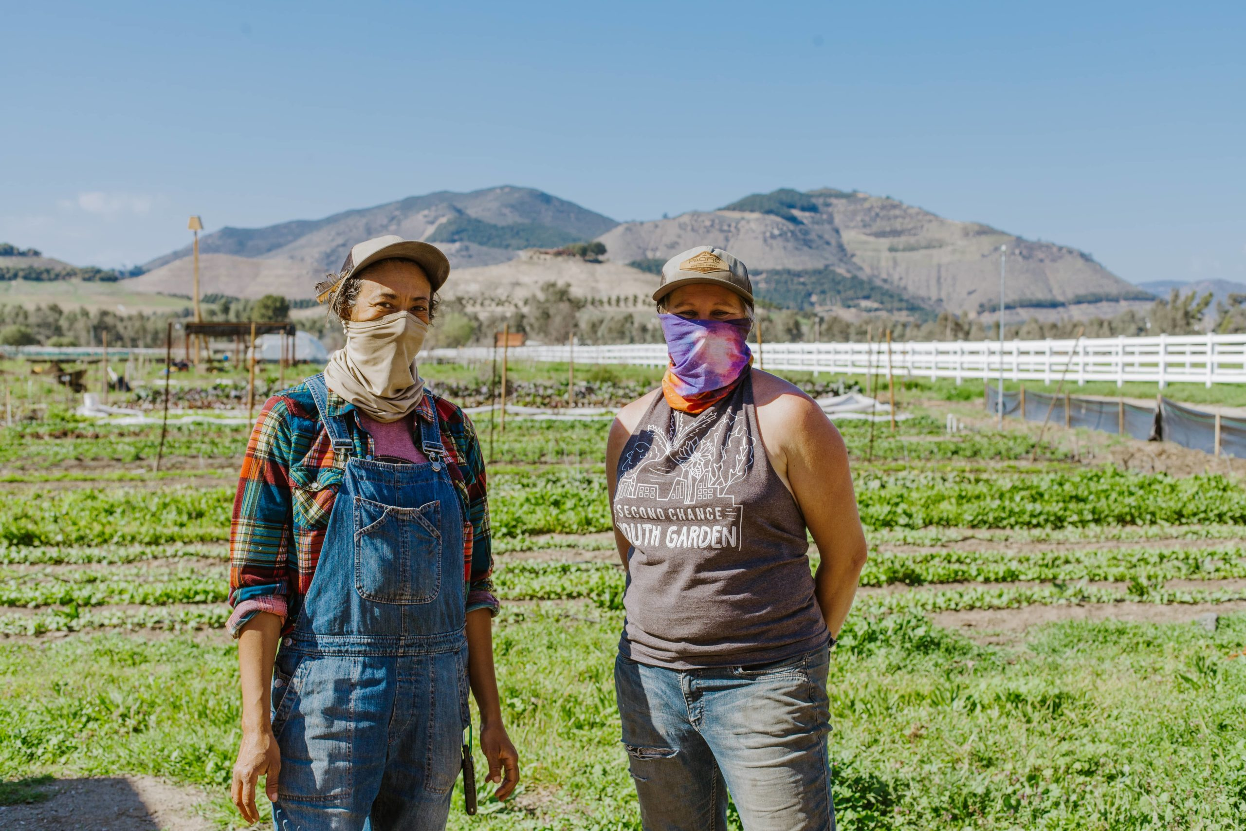 Two women standing on a farm with some hills on the background